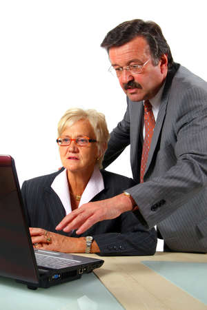 Team Working On Laptop - A business woman and a man in front of a laptop on a desk. The man explains something to the woman. Isolated over white. Stock Photo - 3814511