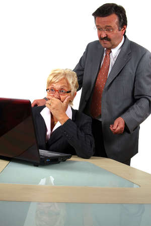 Senior Business Team Working On Laptop - A business woman and a man in front of a laptop on a desk. The man explains something to the woman. The woman is shocked. Isolated over white.  Stock Photo - 3829194