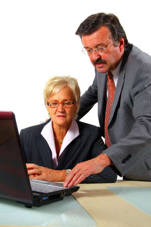 Business Team Working In Office - A business woman and a man in front of a laptop on a desk. The man explains something to the woman. Isolated over white. Stock Photo - 3833452