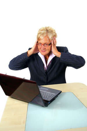 Senior Businesswoman Sees Shocking News - A businesswoman in her sixties in front of a laptop shocked with her hands on her head. Isolated over white.  Stock Photo - 3833449