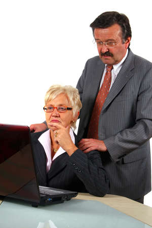 Working Senior Businessteam - A business woman and a man in front of a laptop on a desk. The man explains something to the woman. Isolated over white. Stock Photo - 3833448