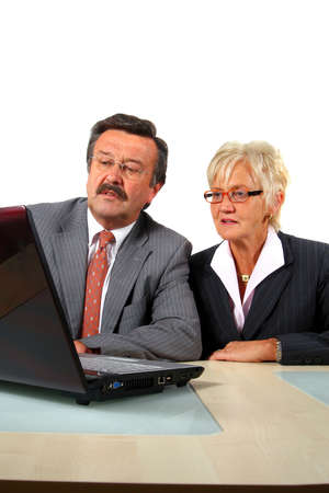 Mature Team - A senior businesswoman in her fitifties is working on a laptopt in an office. Isolated over white. Stock Photo - 3850794