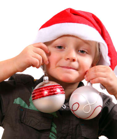 Little Helper Of Santa - A young boy with christmas balls in his hand and a christmas hat. Isolated over white.  photo