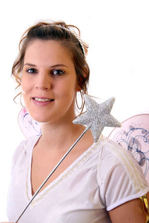 Getting Ready For Christmas - A young beautiful cute and happy Christmas fairy with wings and a magic wand getting ready for Christmas! Isolated over white! photo
