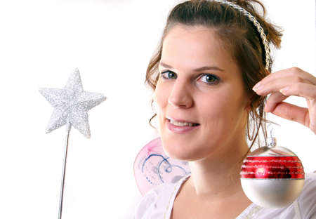 Chrismtas Fairy - A young beautiful cute and happy Christmas fairy with wings and a magic wand getting ready for Christmas! Isolated over white! photo