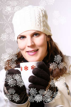 Young Snowelf - A young woman holding a cup of tea in winterclothes with snowflakes. Isolated over white space (for text). Stock Photo - 3917817