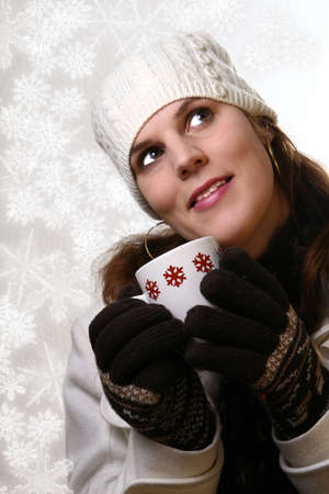 Christmas Beauty - A young woman holding a cup of tea in winterclothes with snowflakes. Isolated over white space (for text). Stock Photo - 3917807
