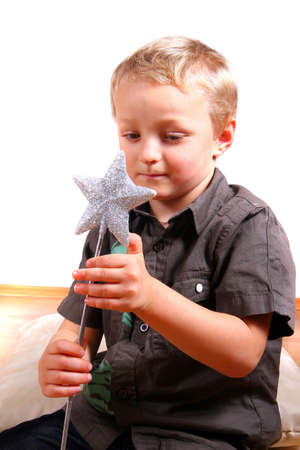 Boy With Magic Wand - Young boy with a magic christmas wand in his hands. Isolated over white. Stock Photo - 3978817