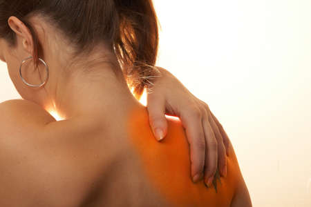 nape: Severe Shoulder Pain - A young woman holds her back in pain! The area on the shoulder is higlighted to symbolize the pain.
