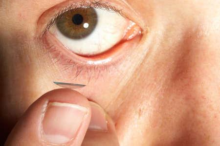 contact lense: Contact Lense - Closeup view of a mans brown eye while inserting a corrective contact lens on a finger.  Stock Photo