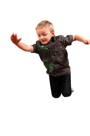 Cute Boy Jumping - A young boy jumps in the air! Slight motion bluriness is intended. Isolated over white photo