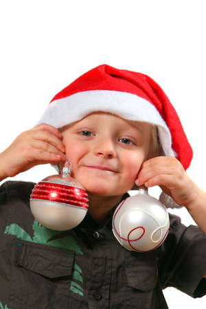Funny Christmas Boy - A young boy with two christmas balls in his hands and a christmas hat on is goofing around. Isolated over white.  photo