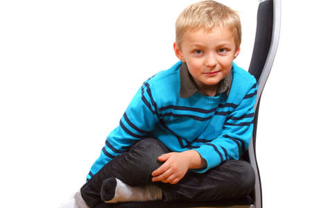 Cute Young Boy - A young happy boy on a chair. Isolated over white.  photo
