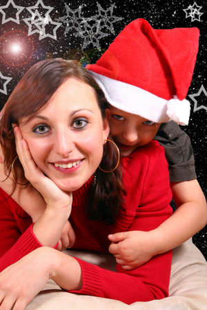 Xmas - Young mom with her son with a christmas hat on. Over a christmas background.  photo