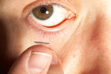 opthalmology: Closeup view of a mans brown eye while inserting a corrective contact lens on a finger. Focus is on the lense!