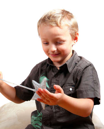 Young boy with a magic christmas wand in his hands. Isolated over white.  photo