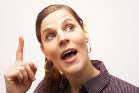 realiseren: Jonge vrouw met haar vinger op haar hoofd - met een idee of een goede gedachte!