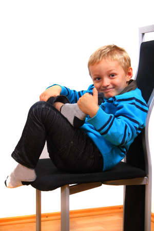 A young happy boy on a chair. Isolated over white. photo