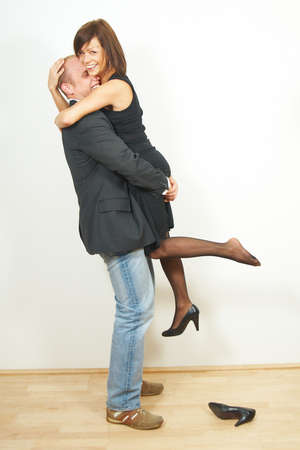 A young man lifts his cute girlfriend. They are in love and very happy.