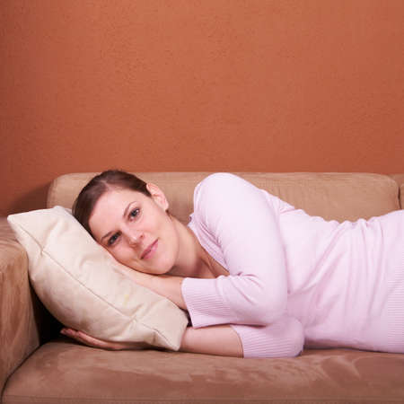 A young woman is lying on a couch and relaxing. photo