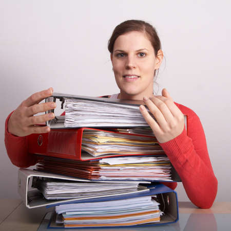 A young woman in front of a stack of paperwork. A lot of copyspace. photo