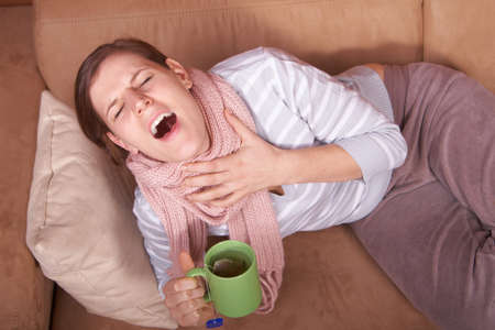 A young woman is sick. She is lying on the couch, sneezing. She has a tea in her hand. photo
