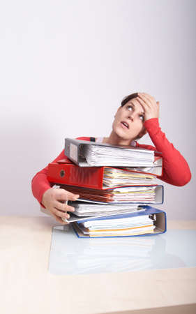 A young and beautiful female student is stressed with a lot of paperwork in front of her. A lot of copyspace. photo