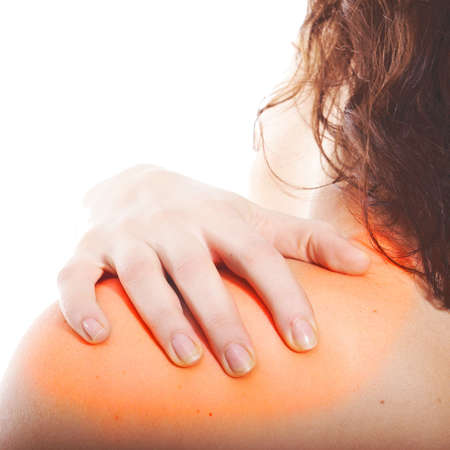 A young woman holds her back in pain! The area on the shoulder is highlighted to symbolize the pain. photo