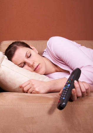 A young woman sleeping on a sofa in front of a TV with the remote control slipping out of her hand. Lots of copyspace. photo