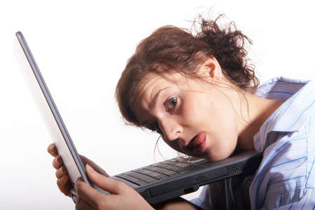 A young woman at home sitting on the floor with her laptop. She is very frustrated. photo