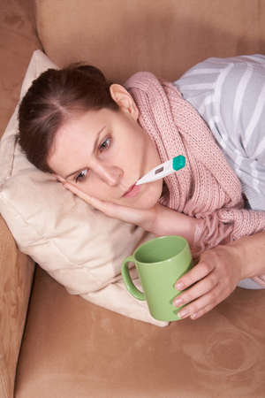 A young sick woman with a thermometer in her mouth and with a cup of tea in her hand.  Stock Photo - 4165133