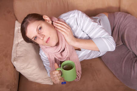 affliction: A young woman is sick. She is lying on the couch and is sneezing. She has a tea in her hand. Stock Photo