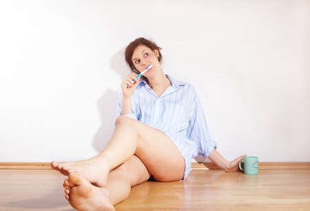 A young woman is brushing her teeth in the morning while sitting on the floor. photo
