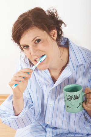 A young woman is brushing her teeth in the morning. photo