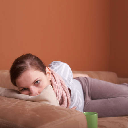A young woman is sick. She is lying on the couch. She has a tea. A lot of copyspace. photo