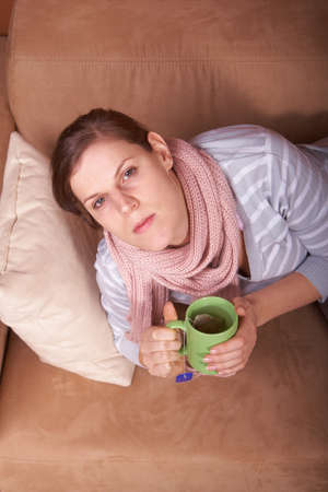 A young woman is sick. She is lying on the couch and is sneezing. She has a tea in her hand. photo