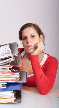 Young woman working on a huge amount of papers. photo