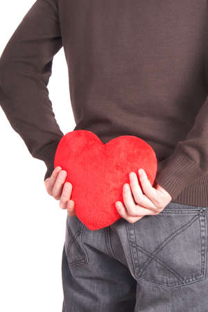 A young man holds a heart shaped pillow behind his back which he gives as a present to his girlfriend for valentines day. Isolated over white. photo