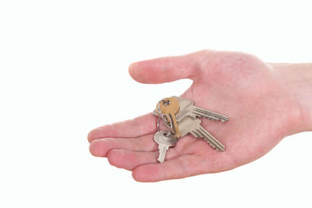 A hand is giving someone a bunch of keys. Isolated over white. photo