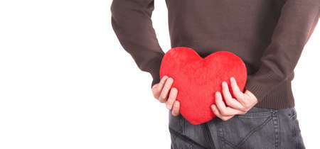 A young man holds a heart shaped pillow behind his back which he gives as a present to his girlfriend for valentines day. Isolated over white. Lot of white copyspace left. photo