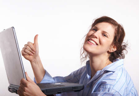 A young woman at home sitting on the floor with her laptop. She is very happy and gives a thumb up sign. Stock Photo - 4204349