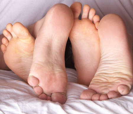 Four feet in a bed. A young couple is having fun.