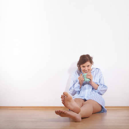 flat foot: A young woman is laughing and relaxing while drinking her first cup of coffee in the morning in her new appartment. A lot of copyspace left.