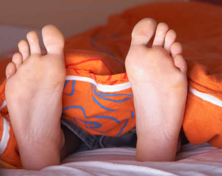 Two feet in a bed. It seems like the woman is sleeping. photo