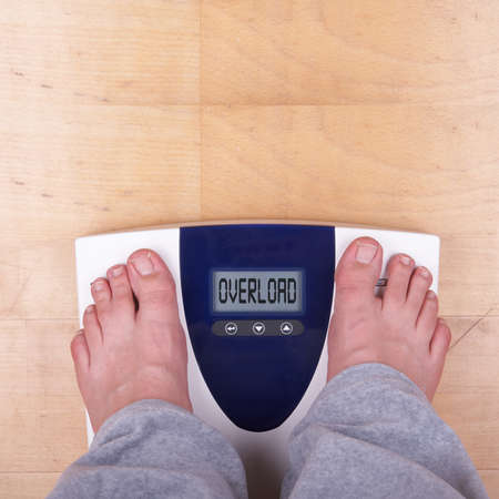 A scale with two feet of the person standing on it on a wooden floor. The scale says:
