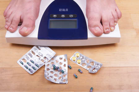 A scale with two feet of the person standing on it - on a wooden floor with pills to loose weight. The scale display is empty - copyspace. photo