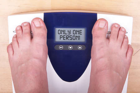 A scale with two feet of the person standing on it on a wooden floor. The scale says: ONLY ONE PERSON!. photo