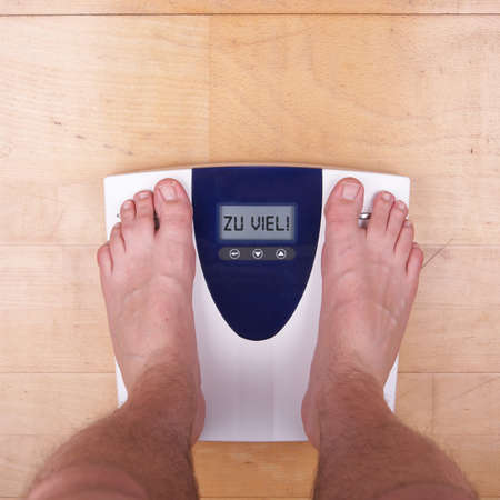 A scale with two feet of the person standing on it on a wooden floor. The scale says: &quot,ZU VIEL&quot,. &quot,Zu viel&quot, = &quot,Too Much&quot, in german. photo