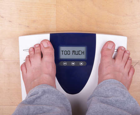 A scale with two feet of the person standing on it on a wooden floor. The scale says: TOO MUCH. photo