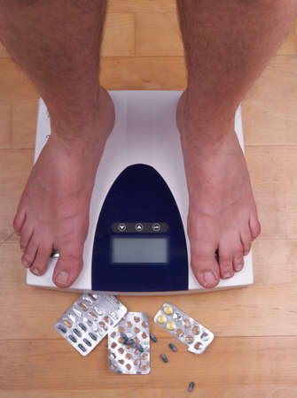A scale with two feet of the person standing on it - on a wooden floor with pills to loose weight. The scale display is empty - copyspace. Stock Photo